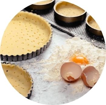 Pasta frolla con uova e farina sul tavolo di lavoro