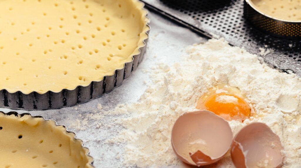 Preparazione di torta con pasta frolla, farina e uova